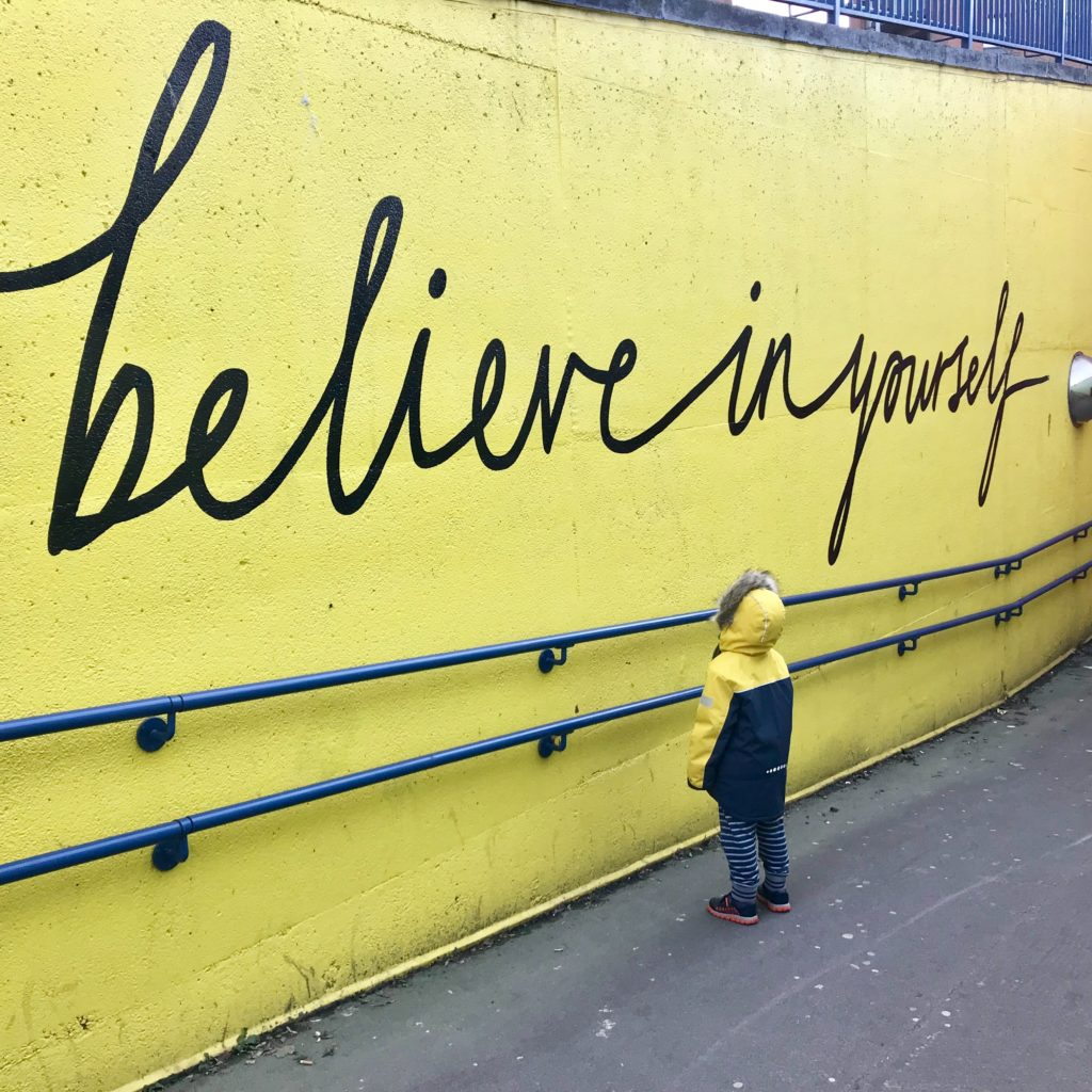 Toddler looking at believe in yourself graffiti. Photo by Katrina on Unsplash.