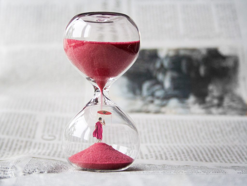 The 3 hours appear like 10 hours! Hourglass with red sand and a monk in it. Time management. Time management tips.